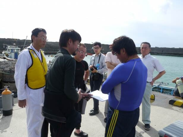 Pre-dive discussion. Mr. Jinbu of the Hakodate Newspaper, third from the left, watches closely.