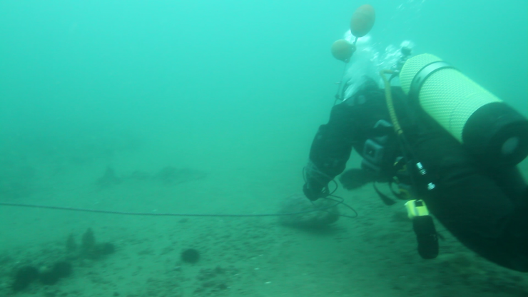 Mr. Yoshida underwater, using a rope to search in a circle around a buoy